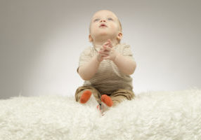 Adorable little baby sitting on the white blanket in praying pose, studio shot, isolated on grey background,