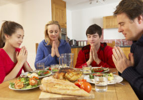 Teenage Family Saying Grace Before Eating Lunch Together In Kitchen