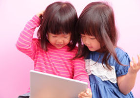 two little girls watching tablet together,Asian
